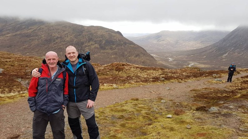 two hikers celebrate at the top of the devils staircase on the west highland way