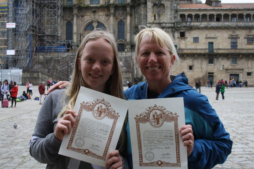 Happy pilgrims with their Camino certificates along the Camino de Santiago.