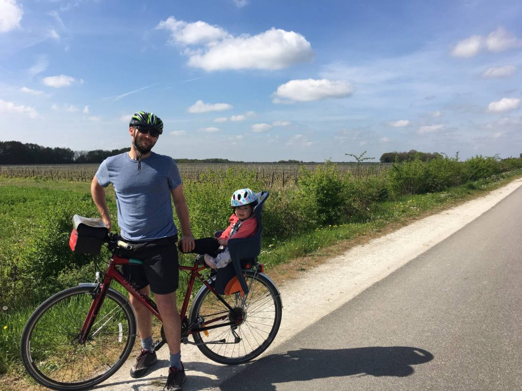 Father and Daughter stand in front of vineyards in the Loire while doing a cycling trip