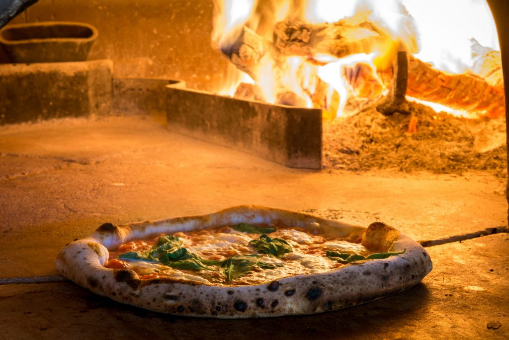 A pizza is removed from a wood fired oven in Italy