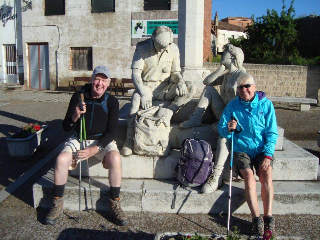 2 pilgrims on the Camino de Santiago pose by statues