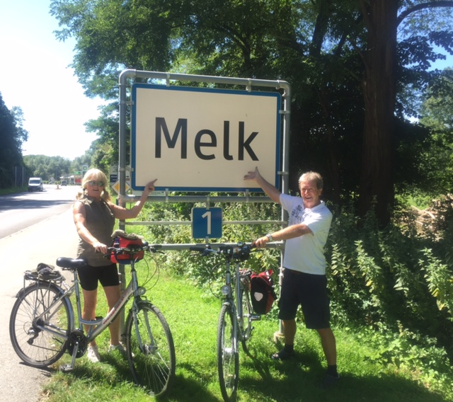 Two cyclists pose beside the sign for Melk on the Danube river path cycling trip