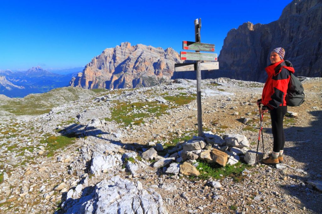 A hiker checks signposts on the Alta Via 1 in the Dolomites, Italy