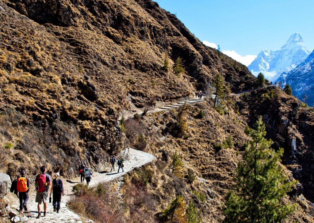 Hikers walking along a narrow path in the Himalayas to Everest Base Camp