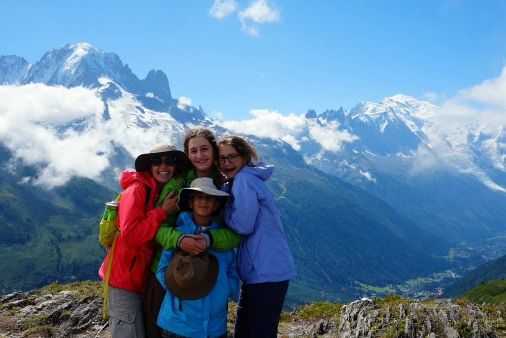 Friends cuddle together for a photograph in front of the Mont Blanc Massif