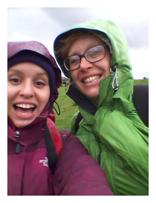 Two happy walkers smile at the camera despite being caught in the rain
