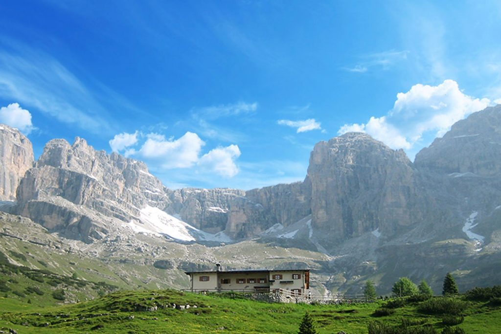 A typical italian mountain hut sits amongst huge stone peaks in the Brenta dolomites