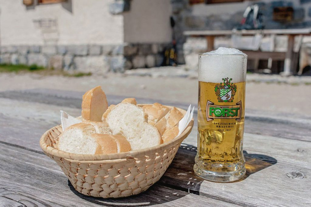 a basket of bread and a cold beer sit on a table in the Brenta Dolomites