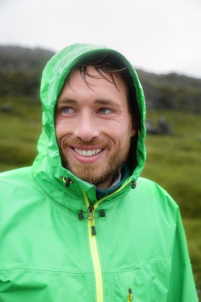 wet man in waterproof jacket smiles