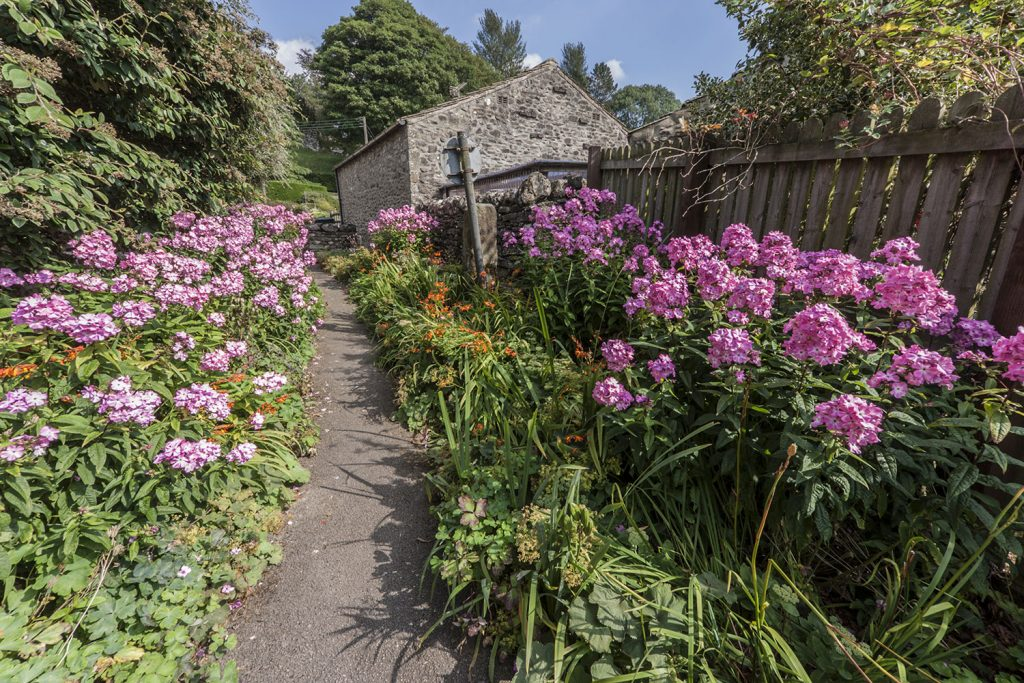 Pink and purple flowers line the path leading to the Yorkshire town of Grassington
