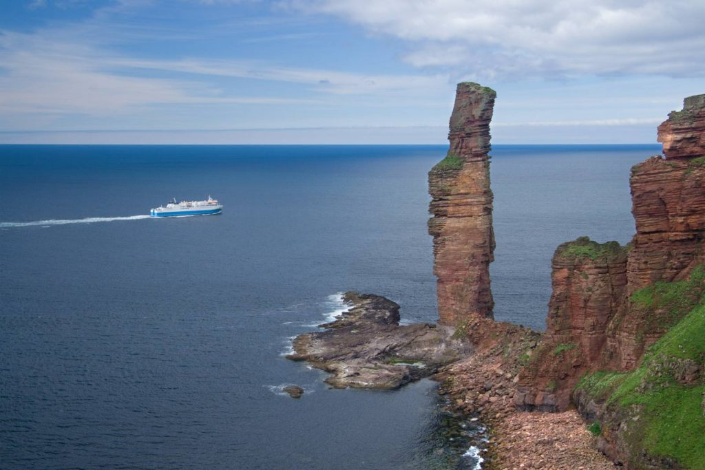 old man of hoy, a large finger of rock poking out of the sea, with a ferry in the background