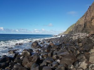 Madeira pebble beach, with breaking waves against Madeira's volcanic hillside