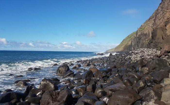 Madeira pebble beach, with breaking waves against Madeira's volcanic hillside