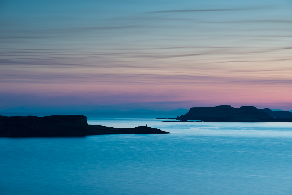 Oronsay island sits in a blue sea with the sunrise tinting the skies