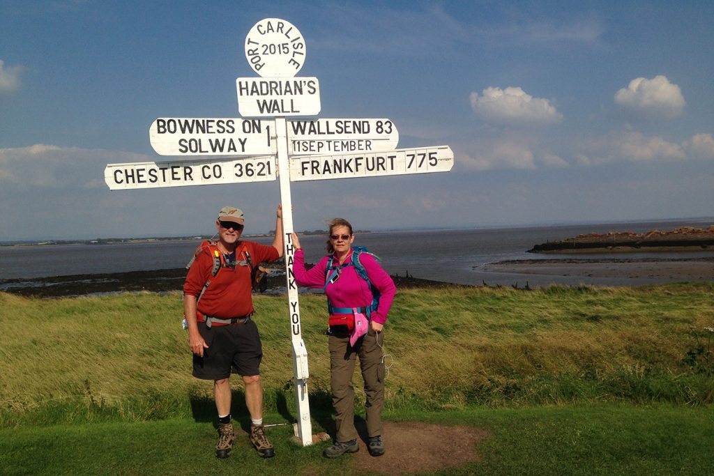 Two hikers under a sign on the Hadrian's Wall Path