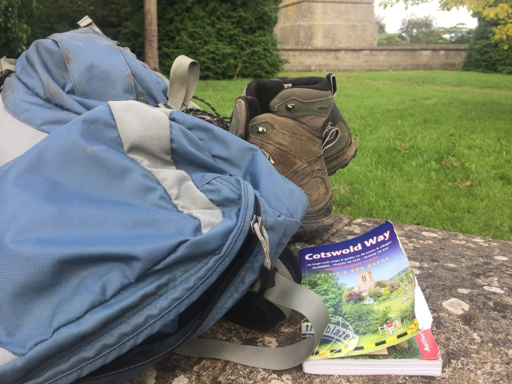 A backpack, book and pair of hiking boots