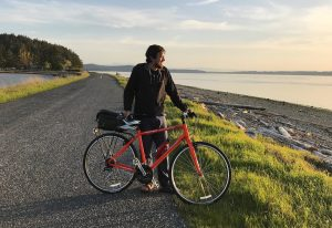 Connor with his bike, sunset, San Juan Islands